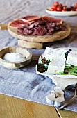 Cheeseboard, salt and cold cuts on linen tablecloth on rustic wooden table