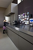 Girl at long counter of designer kitchen made from grey HPL and stainless steel; mementos pinned to wall
