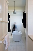 Radiator with towel rails and free-standing bathtub; dark articles of clothing hanging on metal rod