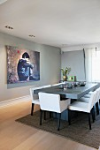 Chairs with white upholstery around pale grey table opposite large artwork on grey wall in modern dining room