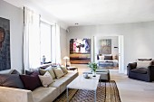 Long sofa with scatter cushions and coffee table on traditional rug in modern living room