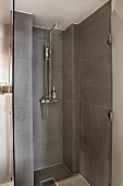 Modern shower area with grey tiles and open glass door