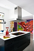 Modern, free-standing kitchen counter with black wooden fronts and stainless steel extractor hood in front of graffito mural on wall