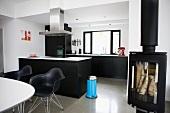 Moderner Wohnraum in Schwarz Weiss - Essplatz mit Klassikerstühlen vor freistehendem Küchenblock und Kaminofen