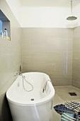 Free-standing bathtub in tiled designer bathroom with floor-level shower