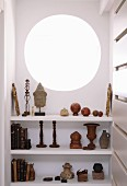 Collection of old books and sculptures on white shelves