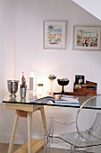 Writing area in mixture of styles with desk made from glass top and wooden trestle and designer plexiglass chair