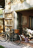 Bicycle with basket in front of stone house with door shutter and view of sofa through open terrace doors