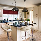 Elegant, cream, country-house kitchen with leather bar stools at breakfast bar