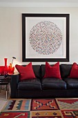 Black leather sofa with red, decorative pillows under an abstract painting