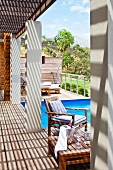Sunny wooden terrace with pergola on concrete pillars next to pool