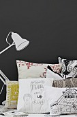 Scatter cushions next to table lamp painted on black wall