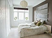 Scatter cushions on double bed against grey-painted wall in bright, modern bedroom