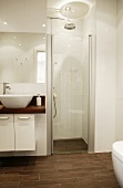 White, modern designer bathroom with separate shower area and brown tiled floor