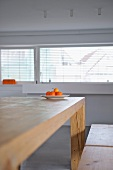 Plate of tangerines on minimalist wooden table in modern interior with half-closed blinds at windows