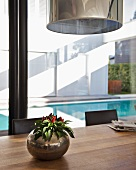 House plant in spherical metal container on wooden table in front of glass wall with view of pool