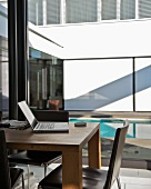 Open laptop on wooden table in front of glass wall with view of courtyard