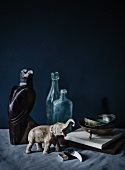 Animal ornaments in stone and wood next to vintage-style bottles against black background
