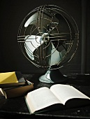 Open book in front of vintage fan on black stone surface