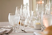 Various stemmed glasses and silver cutlery on white tablecloth