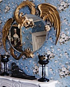 Wooden dragon framing round mirror on papered wall and dark blue glass candlesticks on mantelpiece