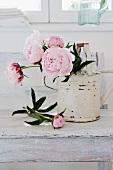 weiße Giesskanne im Vintagelook mit rosa Pfingstrosen auf weisslackierter Ablage