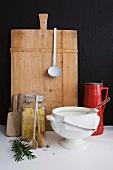Vintage Suppenterrine und Aufbewahrungsglas mit Nudeln vor Schneidebrett an schwarzer Wand lehnend