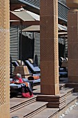 Sun loungers and parasols behind masonry columns on terrace of art deco hotel