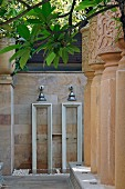 Twin outdoor showers on sandstone wall and impressive stone columns decorated with traditional patterns