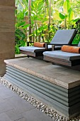 Spa armchairs on stone platform in front of tropical foliage plants