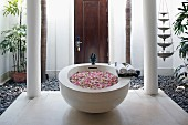 Basin filled with rose petals in courtyard of Oriental spa hotel