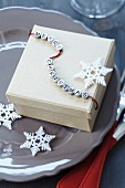 Festive gift box with string of lettered beads reading 'Merry Christmas' and stylised snowflakes