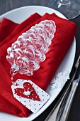 Festive place setting with glass fir cone and paper tag on red linen napkin