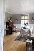 Gedeckter Tisch gegenüber Klavier in grossräumigem Esszimmer mit rustikalem Dielenboden und weisser Holzdecke
