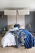 Different coloured blankets on double bed with canopy and upholstered headboards on grey wooden wall in rustic bedroom