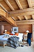 Breakfast tray on double bed below massive wooden ceiling beams in rustic bedroom