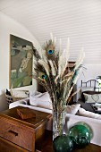 Bouquet of grasses and peacock feathers on retro cabinet; sofa and chair in background