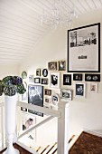 Gallery of photographs on wall of staircase with white-painted wooden elements and mosaic parquet floor