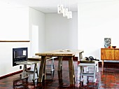 Down-to-earth, improvised living-dining room with glossy, orange tiled floor and dining table made from massive wooden slab on wooden trestles