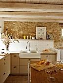 Aufbewahrungsgläser mit Lebensmittel auf Kücheninsel vor Küchenzeile an gefliestem Spritzschutz und Natursteinwand in ländlichem Ambiente