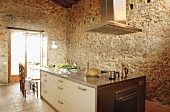 Modern kitchen island in front of rustic stone walls of converted, Spanish country house