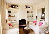 Comfy living room furniture with white slip covers in front of an open fireplace and brick, built in bookshelves with a rustic air