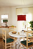 Mediterranean wooden chairs around a breakfast table under an hanging lamp with a red lampshade in front a of a patio door in a white kitchen