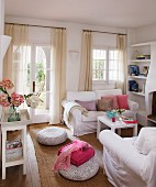 White living room furniture and floor pillows on a sisal rug in a living room with airy curtains at glazed doors and windows