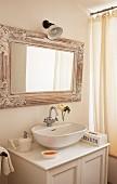 Moderne Waschschüssel auf Vintage Unterschrank und nostalgisch gerahmter Spiegel neben Duschvorhang