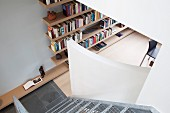 View down wire mesh stairs of floating bookshelves in study