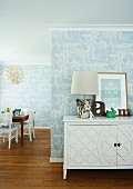 Table lamps with lampshades in natural colors on a white sideboard with carved door in front of a wall with bright blue wall paper with a floral pattern and a view into an open dining room