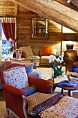 Armchair and footstool in comfortable living room of wooden cabin