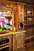Rustic, wooden fitted cupboard with carved details and integrated serving hatch leading to kitchen