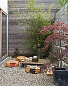 Contemporary Japanese-style courtyard - tea ceremony on improvised table and floor cushions on gravel floor